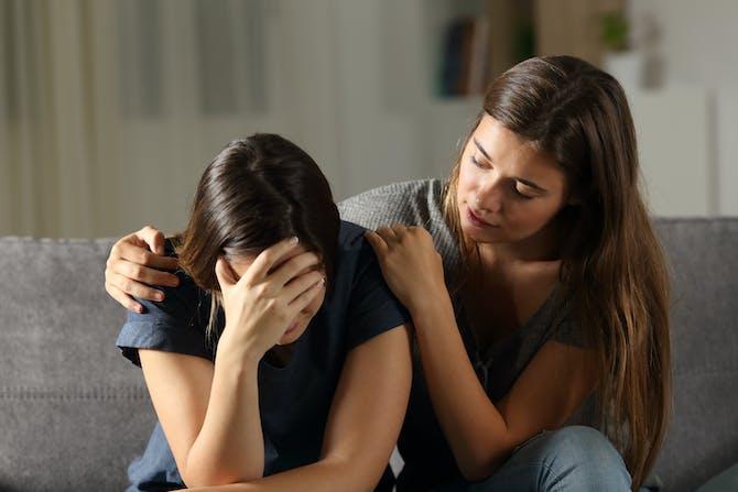 553f17bc797d En kvinde trøster en anden kvinde