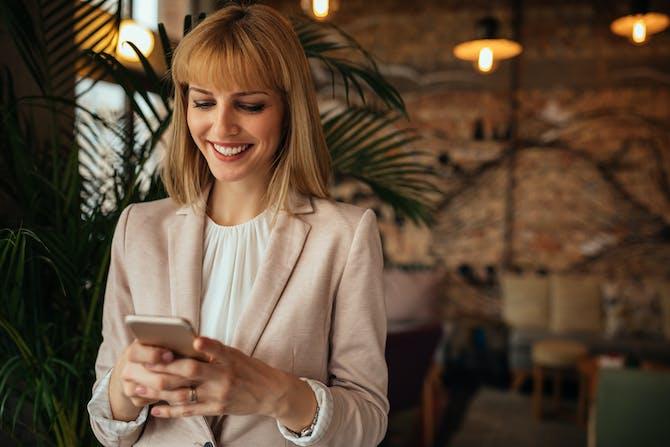 58c64f199b74 En glad kvinde læser en søs sms fra sin veninde