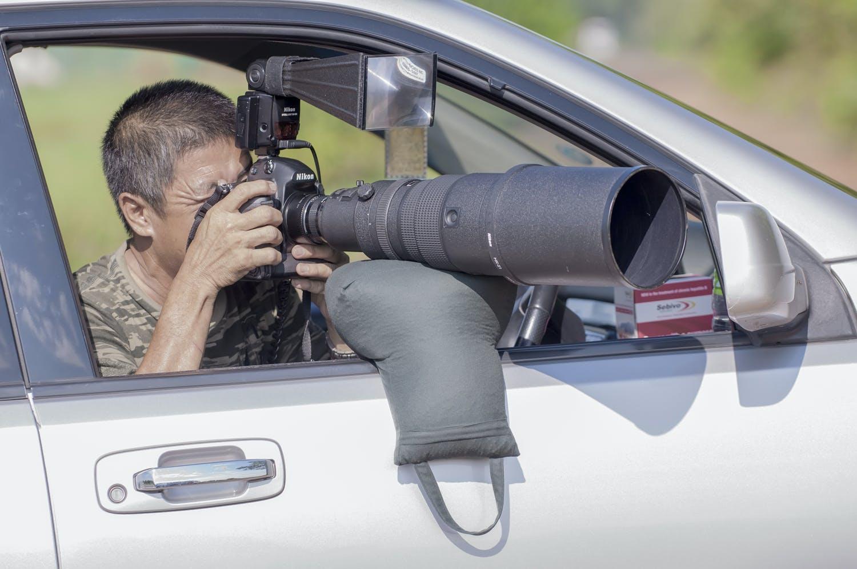 Fotograf i bil bruger sandsæk til at stabilisere it zoomobjektiv.